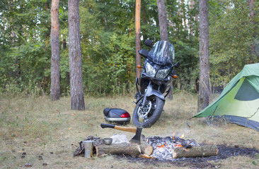Camping in the woods with a tent and a motorcycle.