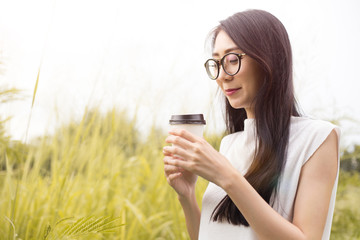 asian women hold paper cup of coffee in the grass field
