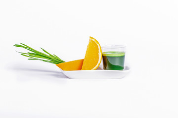Shot glass of wheat grass with orange on a white background