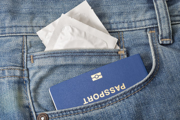Condoms and passport in the pocket of blue jeans closeup