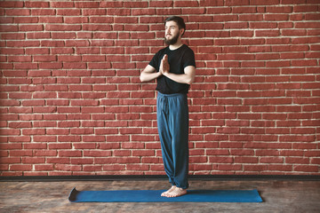 Handsome man doing yoga positions