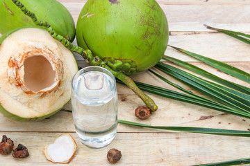 Fresh Coconut Water Drink with coconut leaf on wooden  background