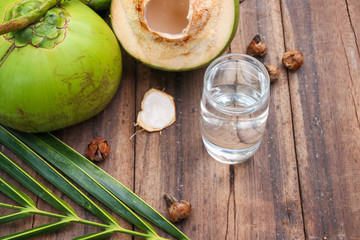 Fresh Coconut Water Drink in glass with coconut leaf on wooden  background