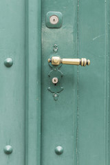 Eine grün bemalte Holztür mit goldfarbenem Griff, Metallnieten und zwei Schlössern. Textfreiraum unten.