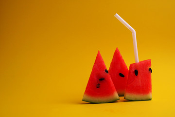 Watermelon sliced, drinking watermelon with white straw on yello