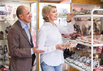 female retiree customer choosing pair of sandals in shoe store