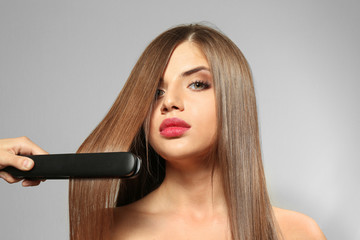 Woman smoothing long hair on light background