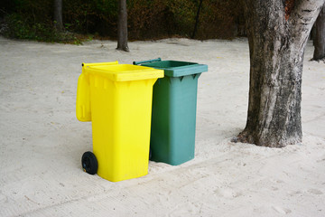 Yellow, Green bins public trash on sand.