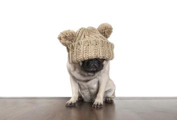 schattige mops hond pup met gebreide muts over ogen, op witte achtergrond