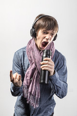 Fun rocker young man enjoying her music listening to a set of earphones.