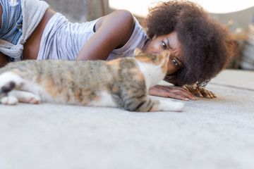 Beautiful afro american woman with her cat on the terrace. Conce