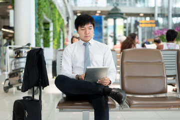 Asian businessman using digital tablet while waiting in lounge