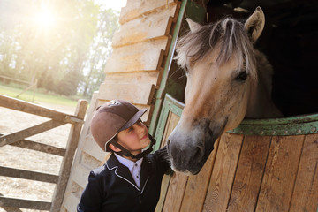 jeune fille 11 ans en tenue d'équitation dans écurie, box avec cheval