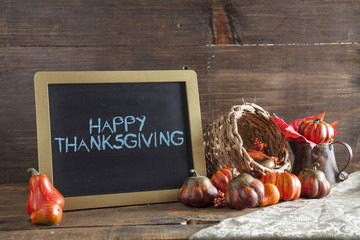 Happy Thanksgiving Written In Blue Chalk On Black Chalkboard Background On Aged Wood Table With Thanksgiving Decorations In Selective Focus.