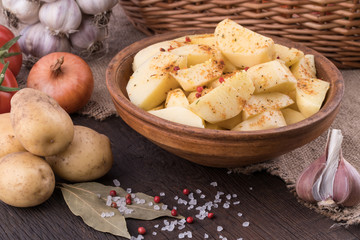 Potatoes in a clay bowl on the old wooden table.
