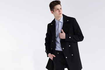 Fashion shot of a young handsome man in black coat.