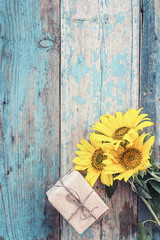 Background with yellow sunflowers and gift box on old wooden boa