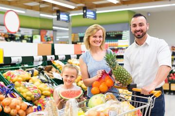 Family choosing fruits in hypermarket.
