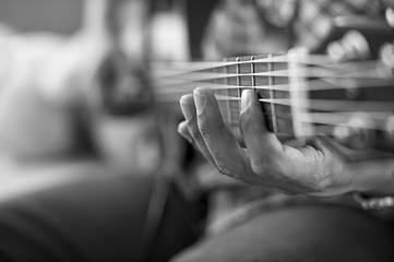 playing acoustic guitar, barre chord,selective focus,black and w