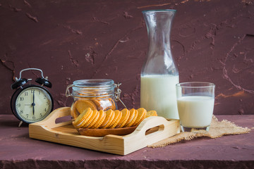 Milk with sandwich cracker and vintage black clock on brown stone table over stone grunge background.