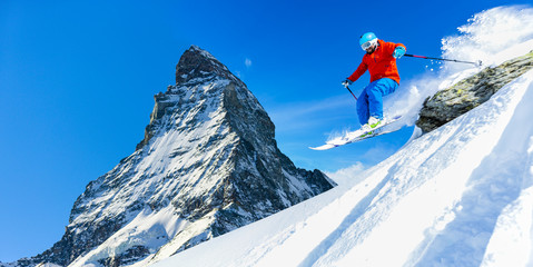 Male skier skiing in fresh snow off ski slope jumping from the rocks on a sunny winter day at high mountain in Swiss Alps. Freeski in powder snow. Matterhorn in background.
