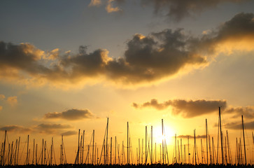gold sunset sky with clouds and yachts at old port.