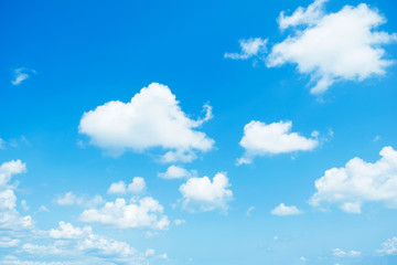 Blue sky with white clouds floating across the full sky.