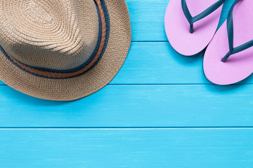 Straw hat and slippers on wood