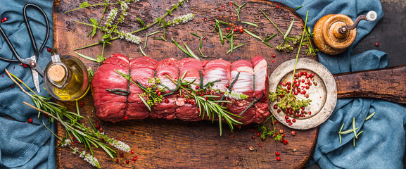 Raw roast beef  with herbs tied with a rope with cooking ingredients, oil  and spices on rustic background, top view, banner Wall mural