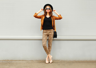 Fashion pretty young woman wearing a retro elegant hat, sunglass Wall mural