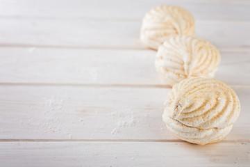close up sweet zephyrs on white wood background.   Bakery products.