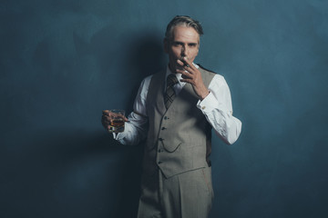 Retro businessman 1920s style smoking cigar and holding glass of
