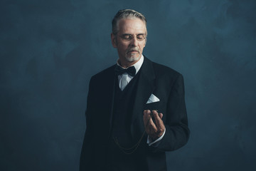 Retro 1920s businessman in black suit looking at pocket watch.