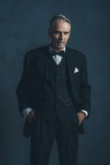 Confident middle aged retro 1920s businessman in black suit with