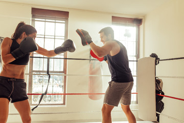 Female boxer with trainer in gym