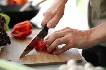 Male hands cutting red pepper on wooden board closeup