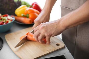 Male hands cutting carrot on wooden board closeup
