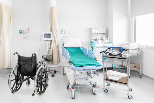 Empty wheelchair parked in hospital room with medical equipement