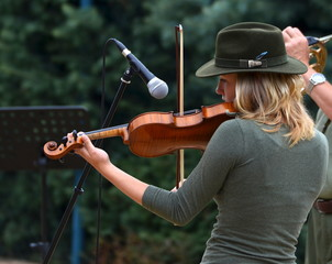 hunter woman playing the violin for the public