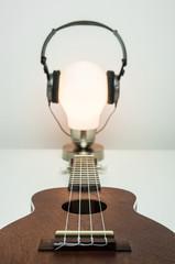 Ukulele skierowane w stronę lampki z założonymi słuchawkami