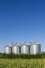 four silver silos in field under   blue sky