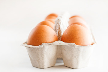 full carton of brown eggs on a white background