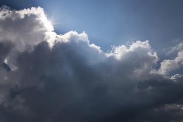 beams of a sun pass through a big storm cloud