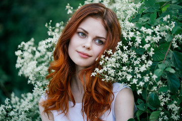 beautiful young woman in a park on a background of flower