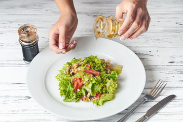 Preparing fresh vegetable salad. Woman pours oil to salad.