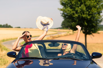 friends having summer joyride in convertible car Wall mural