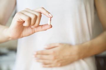 Pills in women's hands. Closeup. Birth control pill, Contraceptive pills, Vitamin pill, pills for better digestion or pills against menstrual pain.