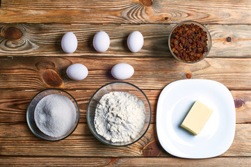 Eggs, sugar, flour, butter, raisins on a large and beautiful kitchen table.