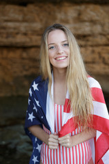 Happy blonde girl smiling at camera with american flag