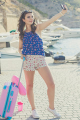 Pretty girl with pink suitcase and cellphone